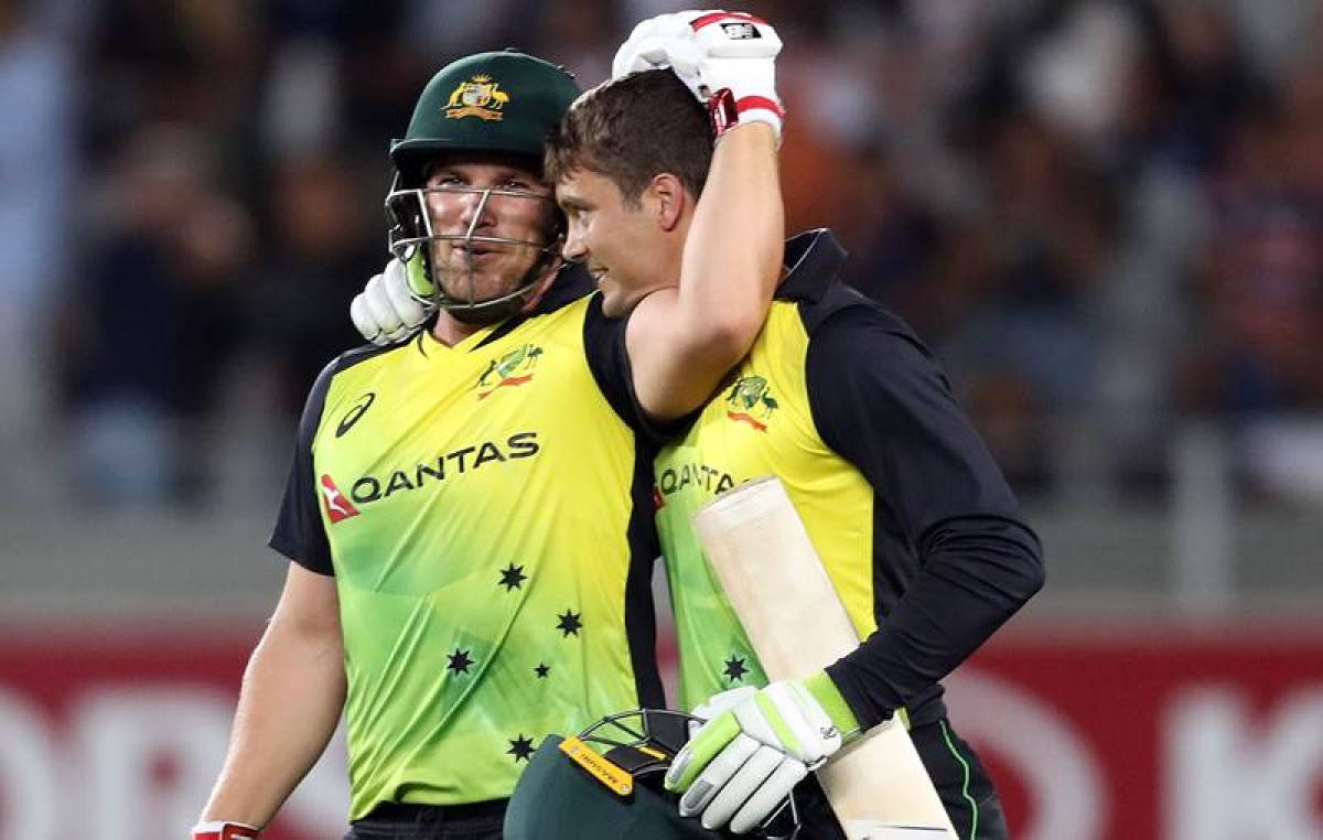 Aaron Finch and Alex Carey celebrate the win during the T20 Tri Series at Eden Park in Auckland / AFP PHOTO / MICHAEL BRADLEY