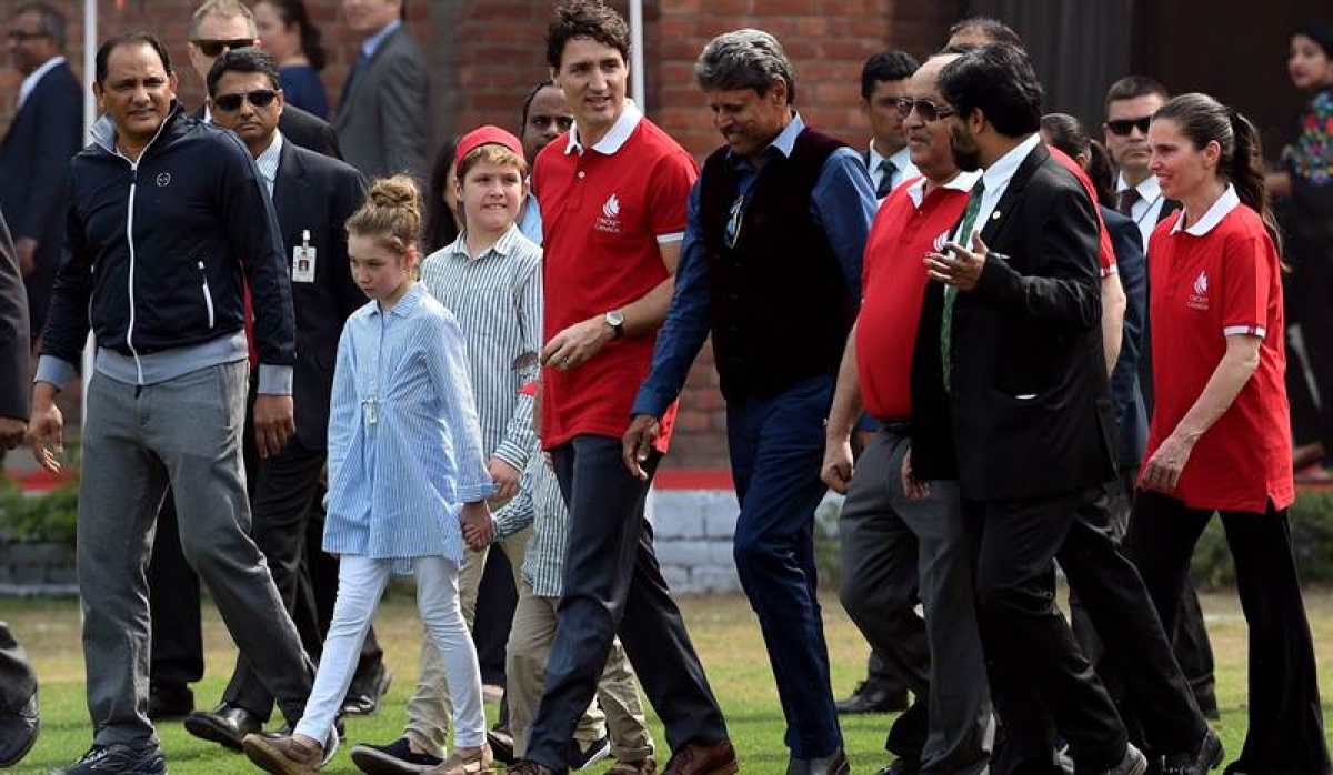 Canadian PM Justin Trudeau (C) and his children Ella-Grace and Xavier join former Indian cricketers Mohammad Azharuddin and Kapil Dev during a cricket event at a school. / AFP PHOTO / MONEY SHARMA