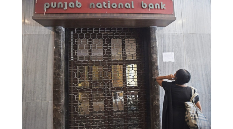 Mumbai: A woman looks on as CBI team seals Punjab National Bank's South Mumbai branch at Brady House in Mumbai on Monday. The PNB fraud case involving jeweller Nirav Modi was allegedly carried out of this branch. PTI Photo by Shashank Parade  (PTI2_19_2018_000088B)