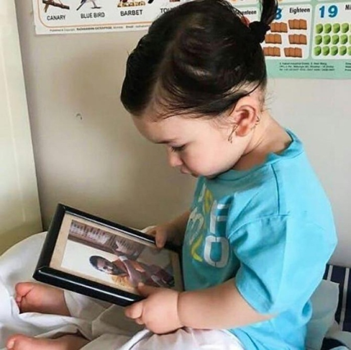 Pony-tailed Taimur Ali Khan staring curiously at dad Saif's picture will surely make your day!