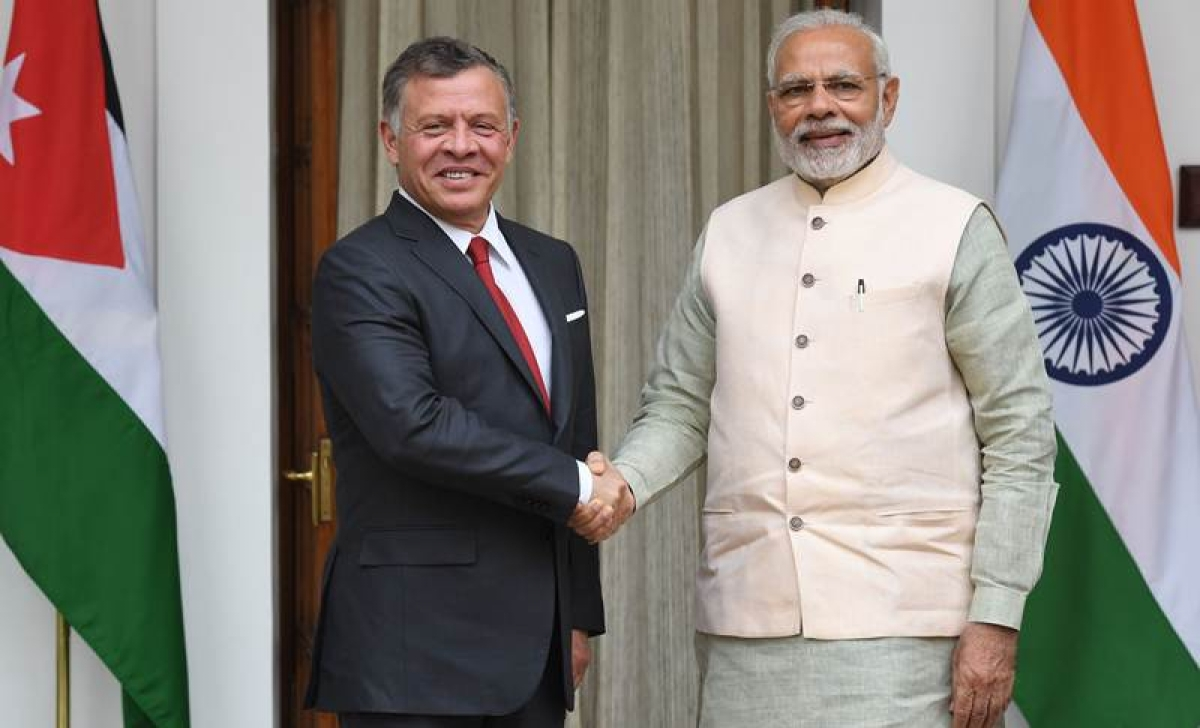 Narendra Modi shakes hands with Jordanian King Abdullah II. / AFP PHOTO / PRAKASH SINGH