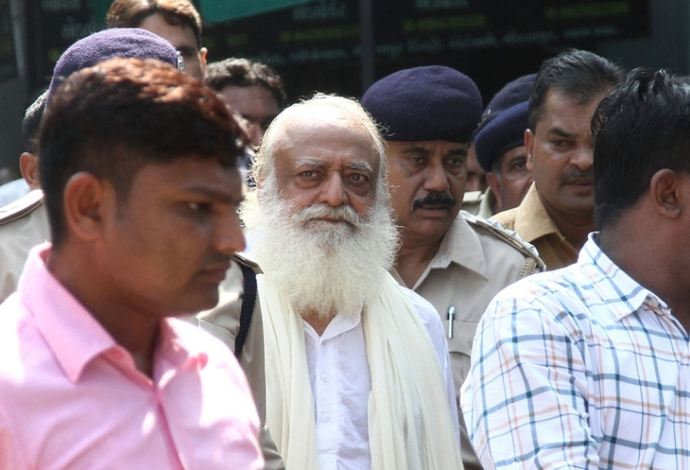 (FILES) In this file photo taken on October 15, 2013 Indian spiritual guru Asaram Bapu (C) is escorted by state police as he leaves a local court in Gandhinagar, some 30 km from Ahmedabad. An Indian guru with millions of followers is in court in Jodhpur on April 25, 2018 accused of raping a teenage devotee on the pretext of ridding her of evil spirits. / AFP PHOTO / SAM PANTHAKY