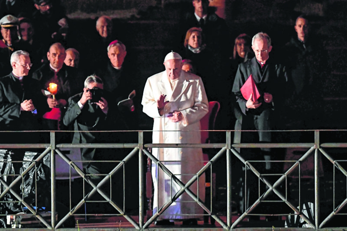 Pope Francis presides the Via Crucis (Way of the Cross) torchlight procession at the Colosseum on Good Friday, on March 30, 2018 in Rome. Christians around the world are marking the Holy Week, commemorating the crucifixion of Jesus Christ, leading up to his resurrection on Easter. / AFP PHOTO / Marco BERTORELLO
