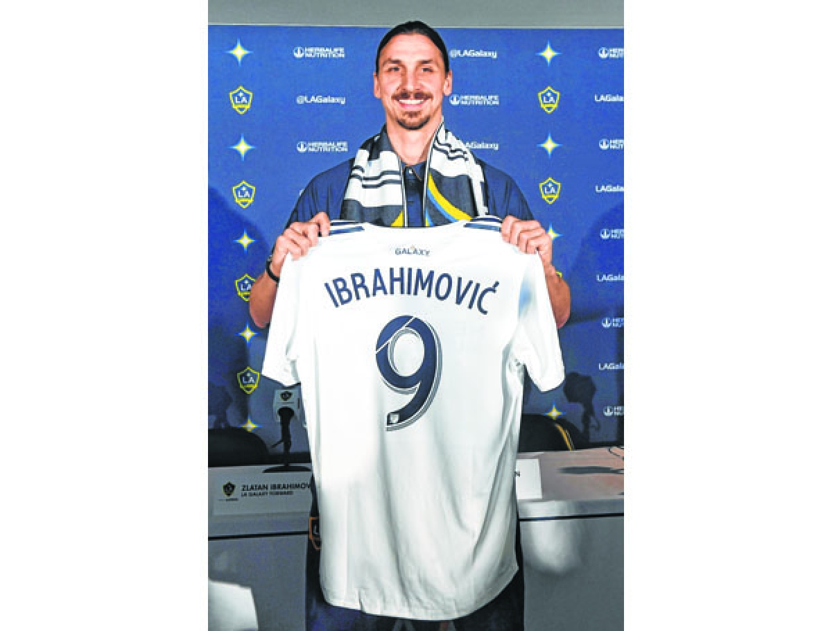 TOPSHOT - Footballer Zlatan Ibrahimovic holds up his new team jersey at his first press conference for his new club LA Galaxy in Los Angeles, California, on March 30, 2018. The 36-year-old Swedish striker's move to MLS from Manchester United was confirmed last week, with Ibrahimovic swiftly vowing to reignite the Galaxy's fortunes after they finished bottom of the league last season.  / AFP PHOTO / Mark RALSTON