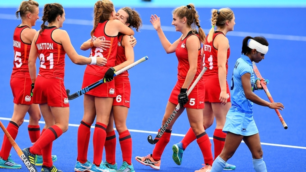 England players celebrate after defeating India in the women's field hockey bronze medal match. / AFP PHOTO / Manan VATSYAYANA