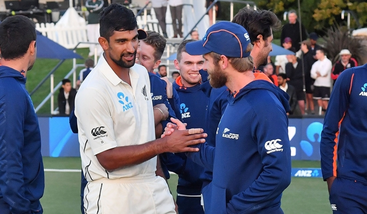 Ish Sodhi celebrates with captain Kane Williamsonas after New Zealand won the Test series against England at Hagley Oval. / AFP PHOTO / Marty MELVILLE