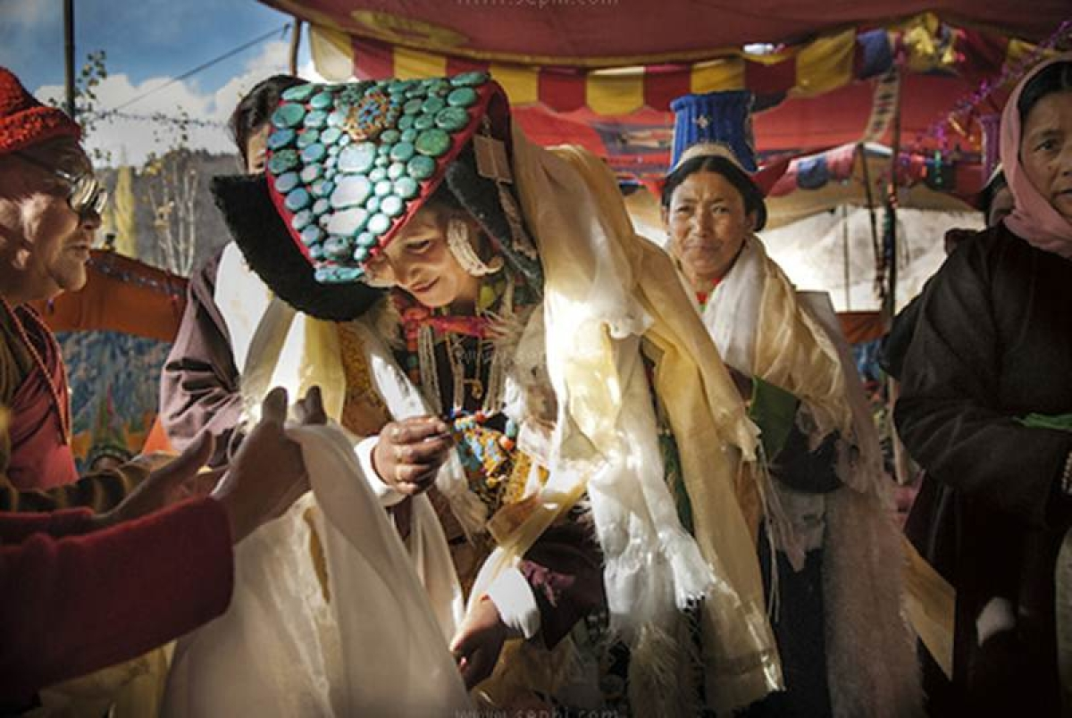 Ladakhi bride receiving scarves as blessings, while her mother watches Ladakh, 2008