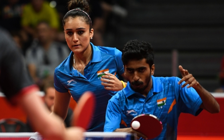 India's Manika Batra (L) and Sathiyan Gnanasekaran (R) play against England's Liam Pitchford and England's Ho Tin-Tin during the mixed doubles semi-final table tennis match at the 2018 Gold Coast Commonwealth Games at the Oxenford Studios venue in Gold Coast on April 14, 2018. / AFP PHOTO / YE AUNG THU