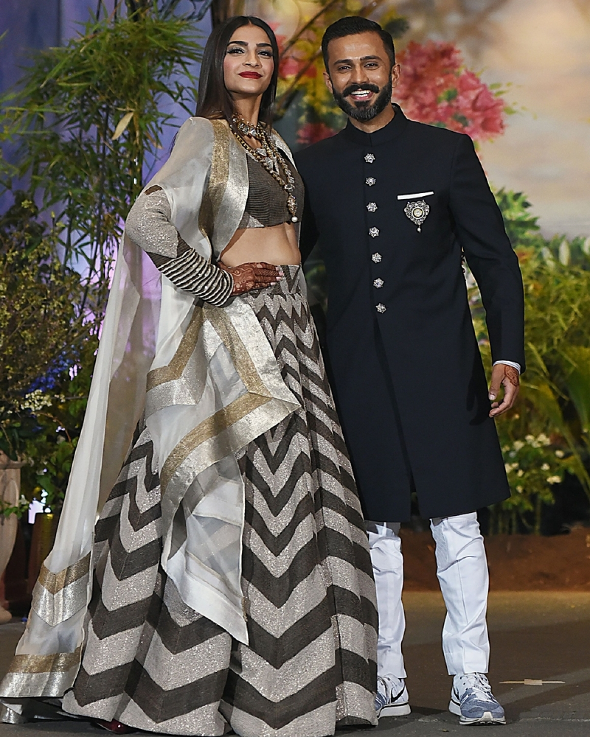 Indian Bollywood actress Sonam Kapoor poses with her husband, businessman Anand Ahuja after their traditional marriage ceremony in Mumbai late on May 8, 2018. / AFP PHOTO