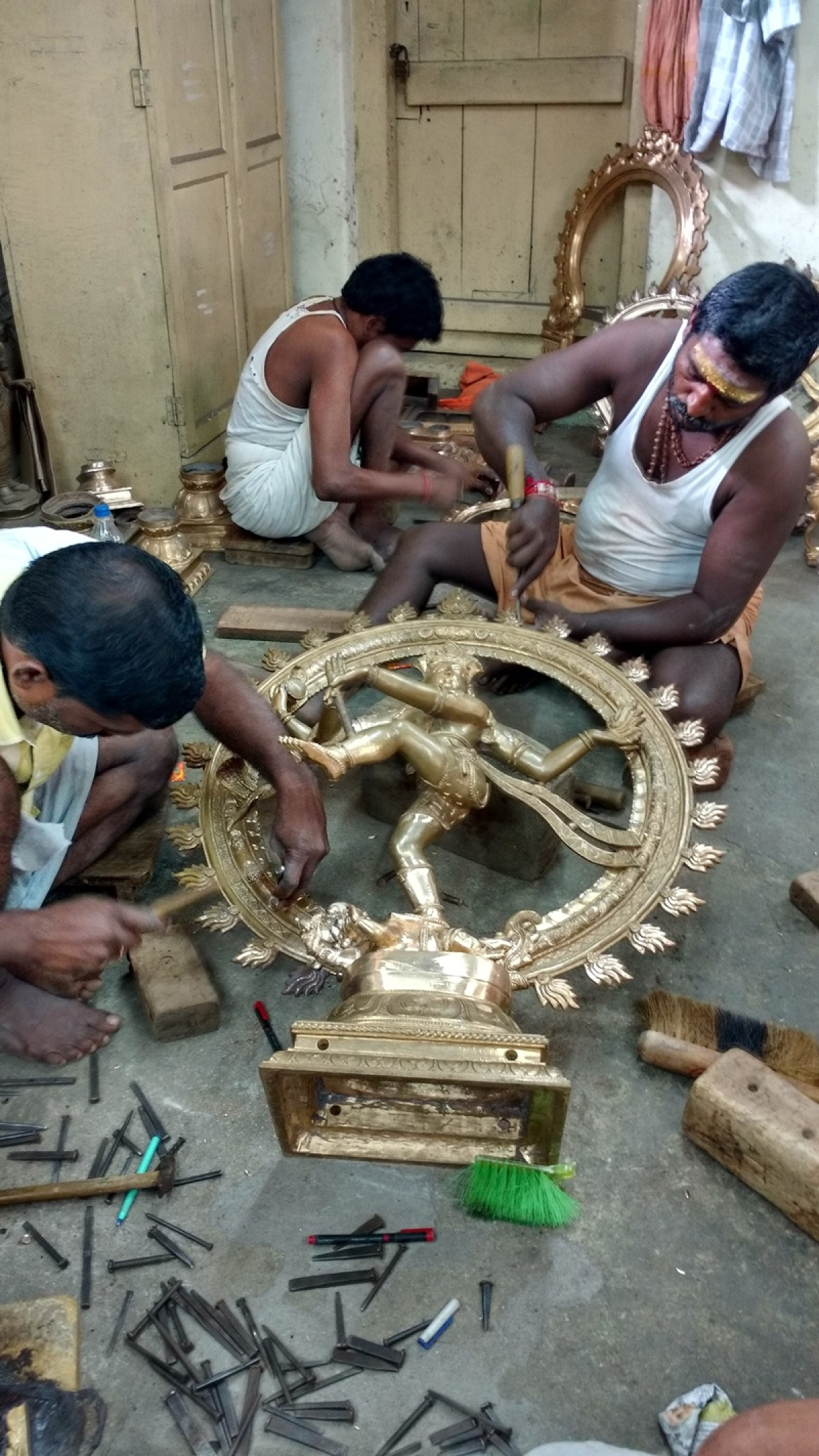 Workers sculpting a Bronze Nataraja at a workshop in Swamimalai