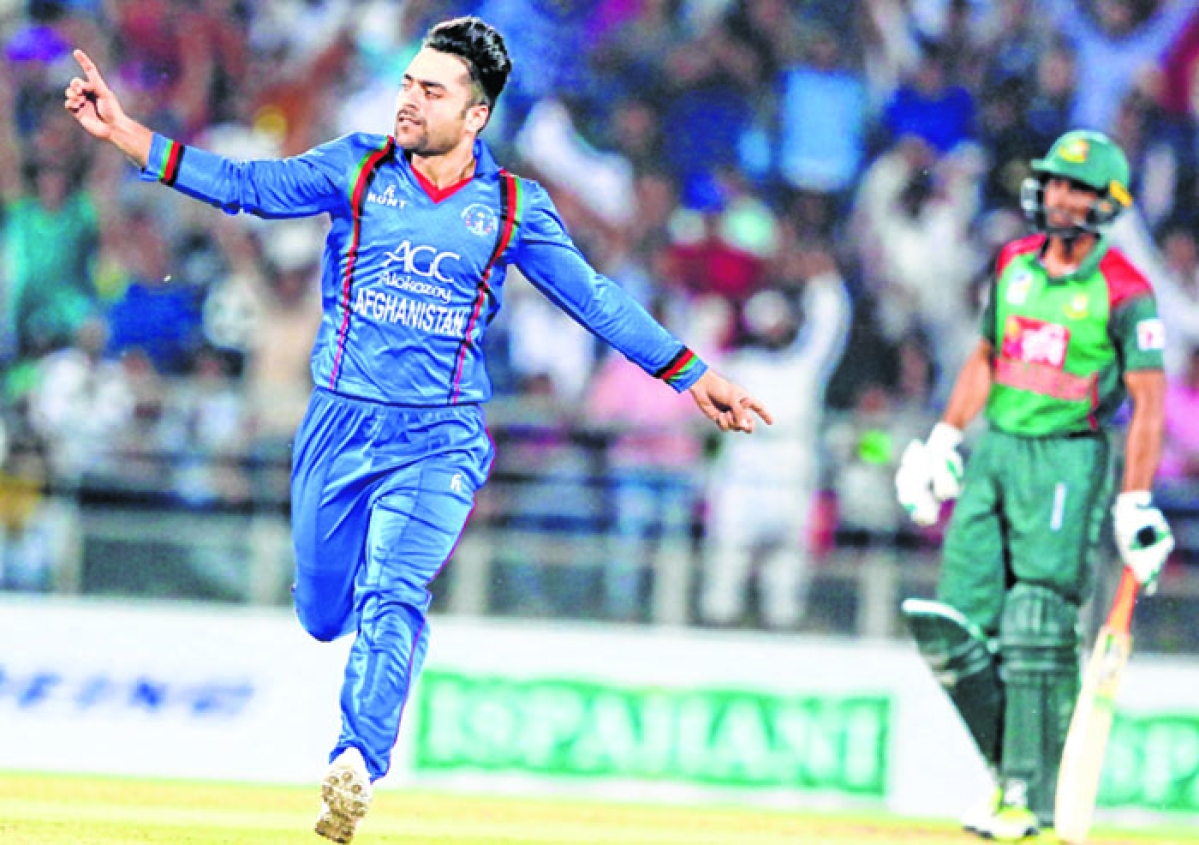 In this photo taken on June 3, 2018, Afghan cricket player Rashid Khan (L) celebrates the wicket during the first Twenty20 International cricket match between Afghanistan and Bangladesh at Rajiv Ghandi International Cricket Stadium in Dehradun. / AFP PHOTO / Kamal Sharma