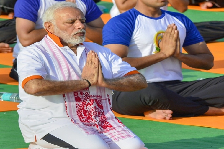 Dehradun: Prime Minister Narendra Modi performs yoga along with thousands of others during a mass yoga event on 4th International Yoga Day at  Forest Research Institute (FRI) ground in Dehradun, on Thursday, June 21, 2018. (PTI Photo/Manvender Vashist) (PTI6_21_2018_000045B)