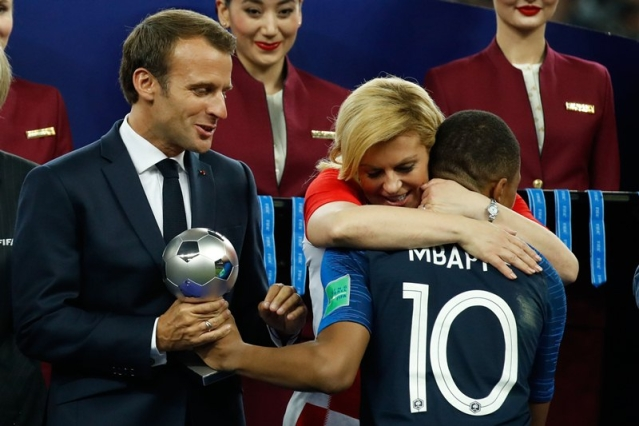 TOPSHOT – France's forward Kylian Mbappe receives the silver ball for best young player from French President Emmanuel Macron and Croatian President Kolinda Grabar-Kitarovic during the medals ceremony after the Russia 2018 World Cup final football match between France and Croatia at the Luzhniki Stadium in Moscow on July 15, 2018.