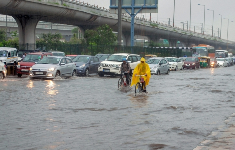 Vehicles ply at waterlogged Greater Noida Expressway during rains. PTI Photo *** Local Caption ***
