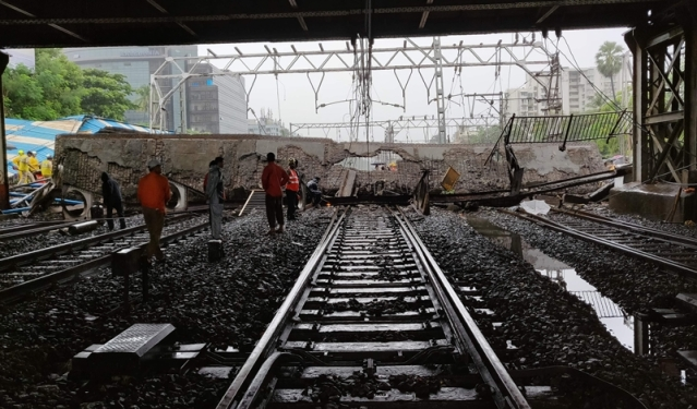 Railway and rescue workers gather around a site where a portion of a pedestrian footbridge collapsed over a railway track. / AFP PHOTO / Punit PARANJPE