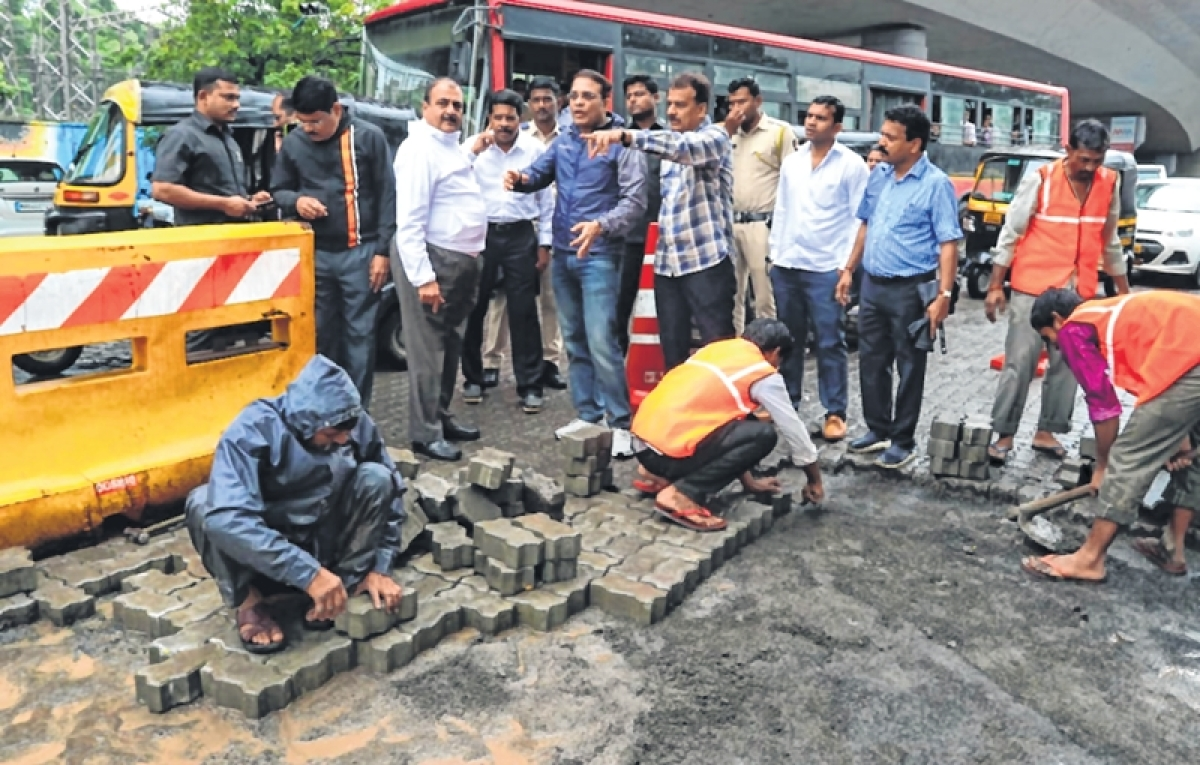 Thane civic chief gets down and dirty, helps team to fill potholes