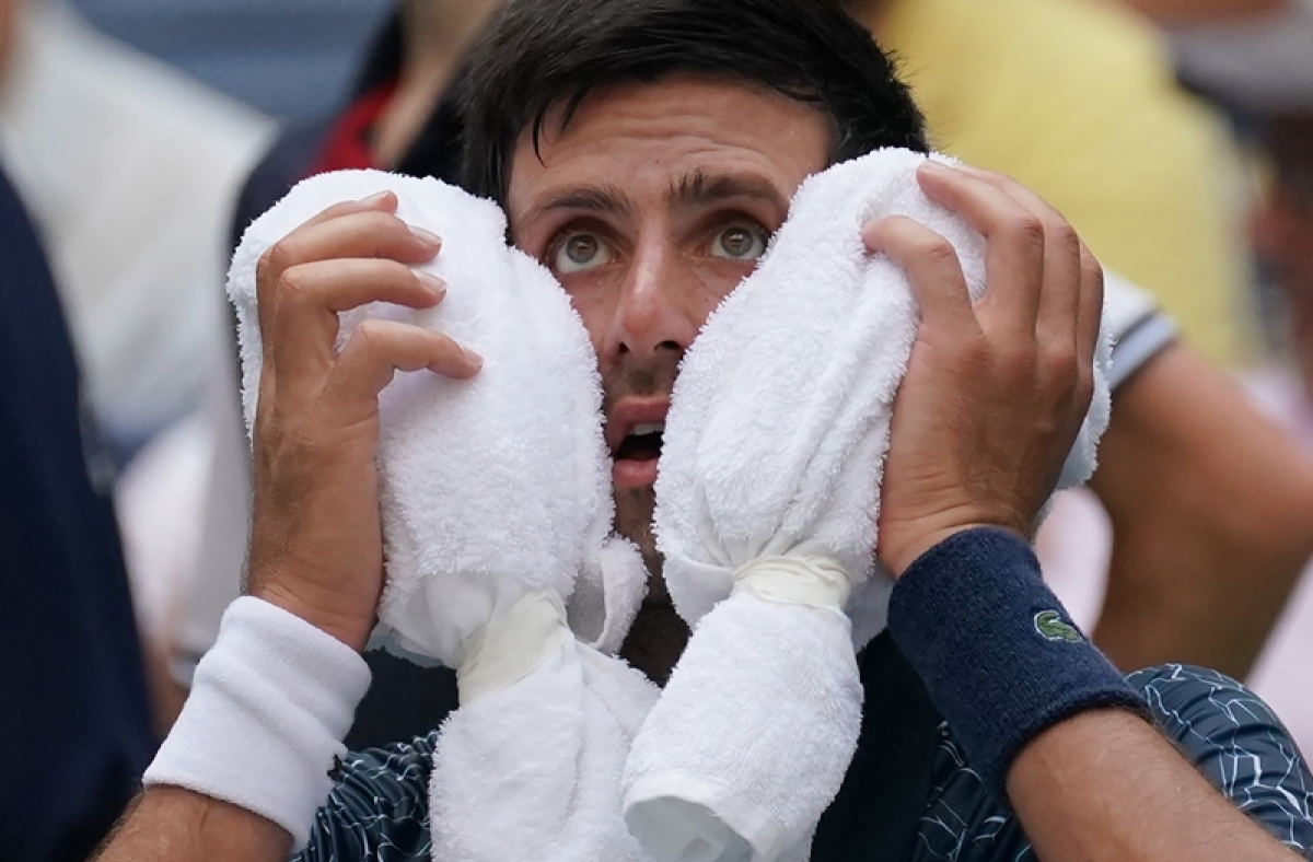 Novak Djokovic  towels off in the heat against Marton Fucsovics of Hungary during their Day 2 2018 US Open match. Photo by TIMOTHY A. CLARY / AFP