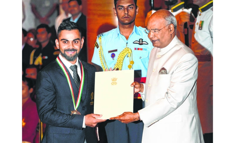 New Delhi: President Ram Nath Kovind confers Rajiv Gandhi Khel Ratna award on cricketer Virat Kohli at the National Sports and Adventure Award 2018 function at Rashtrapati Bhawan in New Delhi, Tuesday, Sep 25, 2018. (PTI Photo/Shahbaz Khan)   (PTI9_25_2018_000140B)