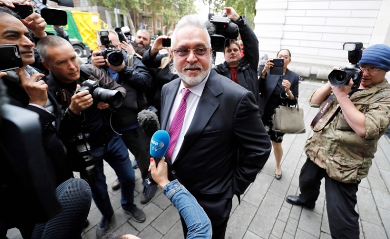 Vijay Mallya speaks to members of the media as he arrives to appear at Westminster Magistrates Court in central London. Photo by Tolga AKMEN / AFP