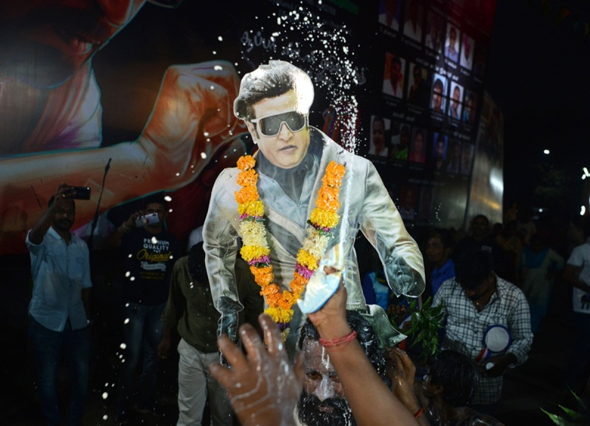 """Indian fans spray milk on a placard displaying the picture of Bollywood star Rajinikanth before attending the early morning show of his new Tamil-language film """"2.0"""" on the first day of its release in Mumbai on November 29, 2018. (Photo by PUNIT PARANJPE / AFP)"""
