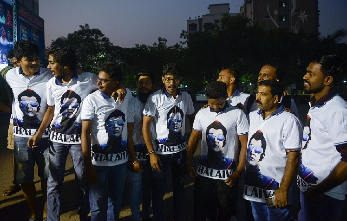 """Indian fans wear T-shirt displaying the image of Bollywood star Rajinikanth as they celebrate before attending the early morning show of his new Tamil-language film """"2.0"""" on the first day of its release in Mumbai on November 29, 2018. (Photo by PUNIT PARANJPE / AFP)"""