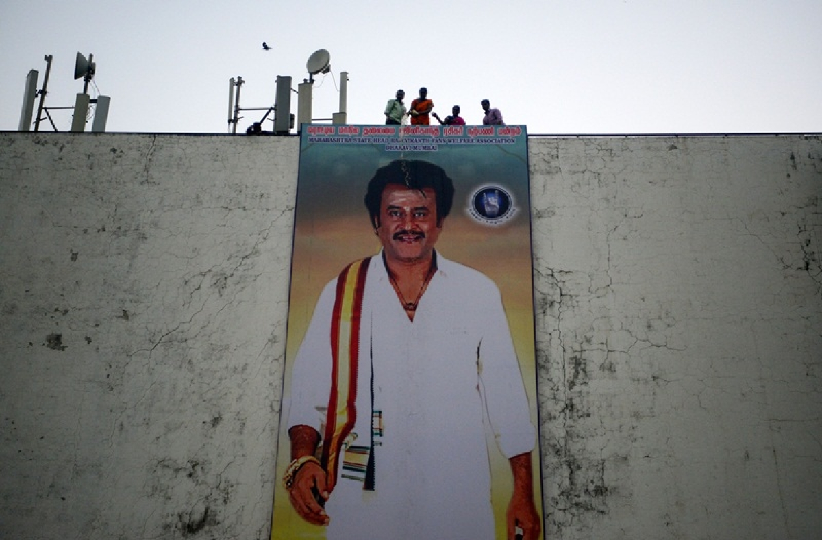"""Indian fans pour milk on a huge poster of Bollywood star Rajinikanth put up outside the cinema hall as they celebrate before attending the early morning show of his new Tamil-language film """"2.0"""" on the first day of its release in Mumbai on November 29, 2018. (Photo by PUNIT PARANJPE / AFP)"""