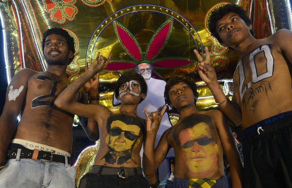 """Indian fans of Bollywood star Rajinikanth display body paint with a portrait of the actor as they celebrate before attending the early morning show of his new Tamil-language film """"2.0"""" on the first day of its release in Mumbai on November 29, 2018. (Photo by PUNIT PARANJPE / AFP)"""