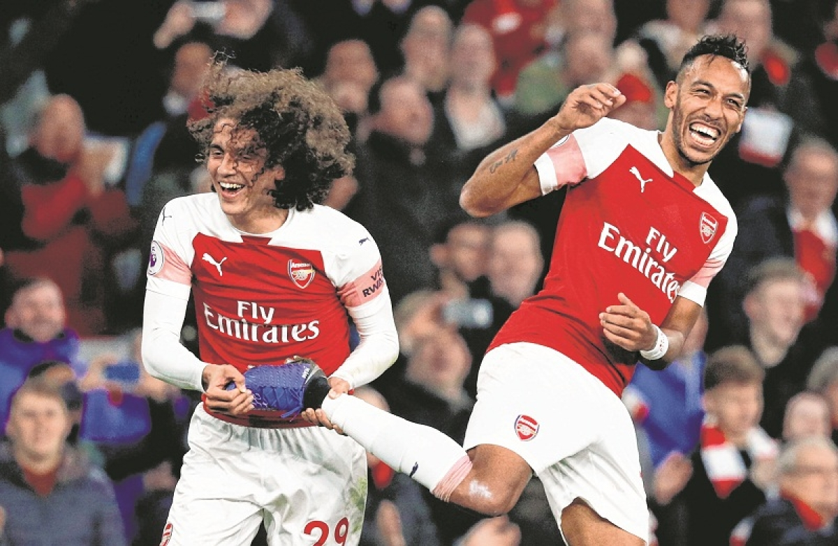 Arsenal's Gabonese striker Pierre-Emerick Aubameyang (R) celebrates with Arsenal's French midfielder Matteo Guendouzi (L) after the English Premier League football match between Arsenal and Tottenham Hotspur at the Emirates Stadium in London on December 2, 2018. - Arsenal won the game 4-2. (Photo by Adrian DENNIS / AFP) / RESTRICTED TO EDITORIAL USE. No use with unauthorized audio, video, data, fixture lists, club/league logos or 'live' services. Online in-match use limited to 120 images. An additional 40 images may be used in extra time. No video emulation. Social media in-match use limited to 120 images. An additional 40 images may be used in extra time. No use in betting publications, games or single club/league/player publications. /