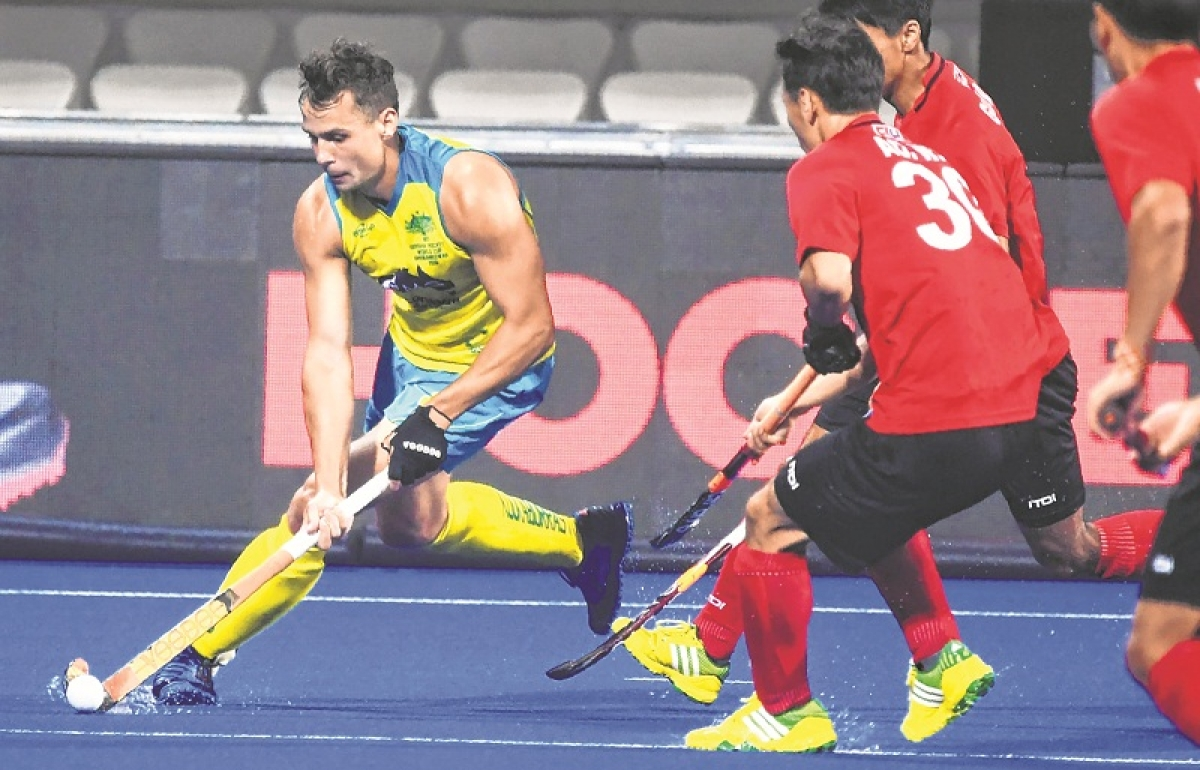 Australia's Corey Craig (L) maneuvers past China players during the field hockey group stage match between Australia and China at the 2018 Hockey World Cup in Bhubaneswar on December 7, 2018. (Photo by Dibyangshu SARKAR / AFP)