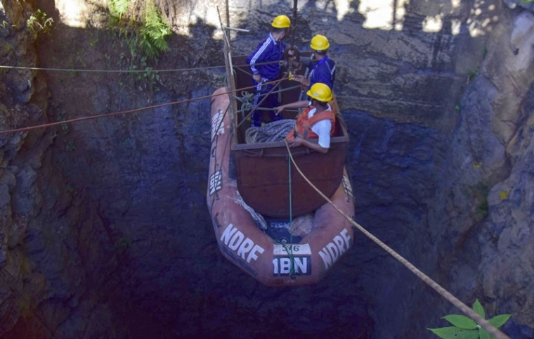 In this file photo Indian Navy divers are lowered into a mine with a pulley during rescue operations to help 15 miners trapped by flooding in an illegal coal mine in Ksan village in Meghalaya. Photo by STR / AFP