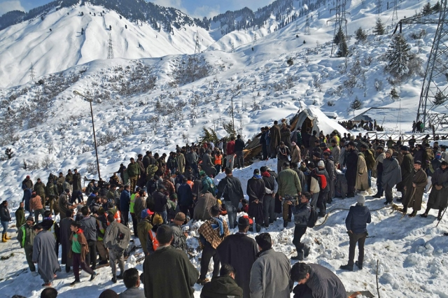 Local residents along with security personnel search the bodies of 10 missing policemen after a snow avalanche hit a police post at Qazigund Jawahar Tunnel in Kulgam district, some 90 km from Srinagar.<br />Photo by STR / AFP