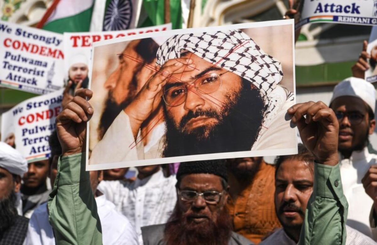 Indian Muslims hold a scratched photo of Jaish-e-Mohammad group chief, Maulana Masood Azhar, as they shout slogans against Pakistan during a protest in Mumbai on February 15, 2019, the day after an attack on a paramilitary CRPF convoy. Photo by Indranil MUKHERJEE / AFP