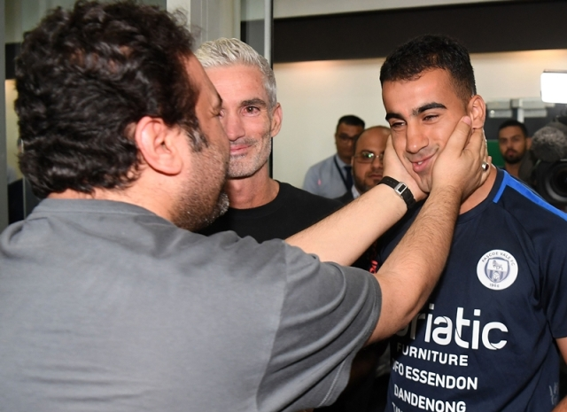 A supporter receives footballer Hakeem al-Araibi (R) upon his arrival at the airport in Melbourne with former Australian football captain Craig Foster (C) on February 12, 2019, following Araibi's departure from Thailand after Bangkok dropped extradition proceedings against him at Bahrain's request. Photo by WILLIAM WEST / AFP