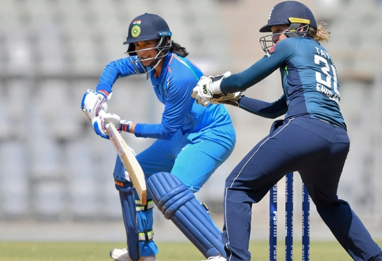 Smriti Mandhana (C) plays a shot as England's Sarah Taylor (R) looks on near the wicket during the second match of the women's ODI. Photo by PUNIT PARANJPE / AFP