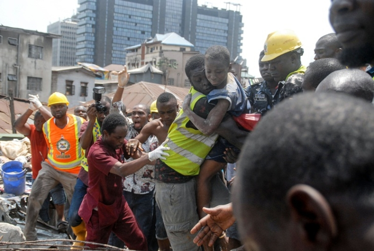 TOPSHOT - Emergency personnel rescue a child at the site of a building which collapsed in Lagos on March 13, 2019. - At least 10 children were among scores of people missing on March 13, 2019 after a four-storey building collapsed in Lagos, with rescuers trying to reach them through the roof of the damaged structure. The children were attending a nursery and primary school on the top floor of the residential building when the structure collapsed. Police said they believed scores of people were trapped under the rubble. (Photo by SEGUN OGUNFEYITIMI / AFP)
