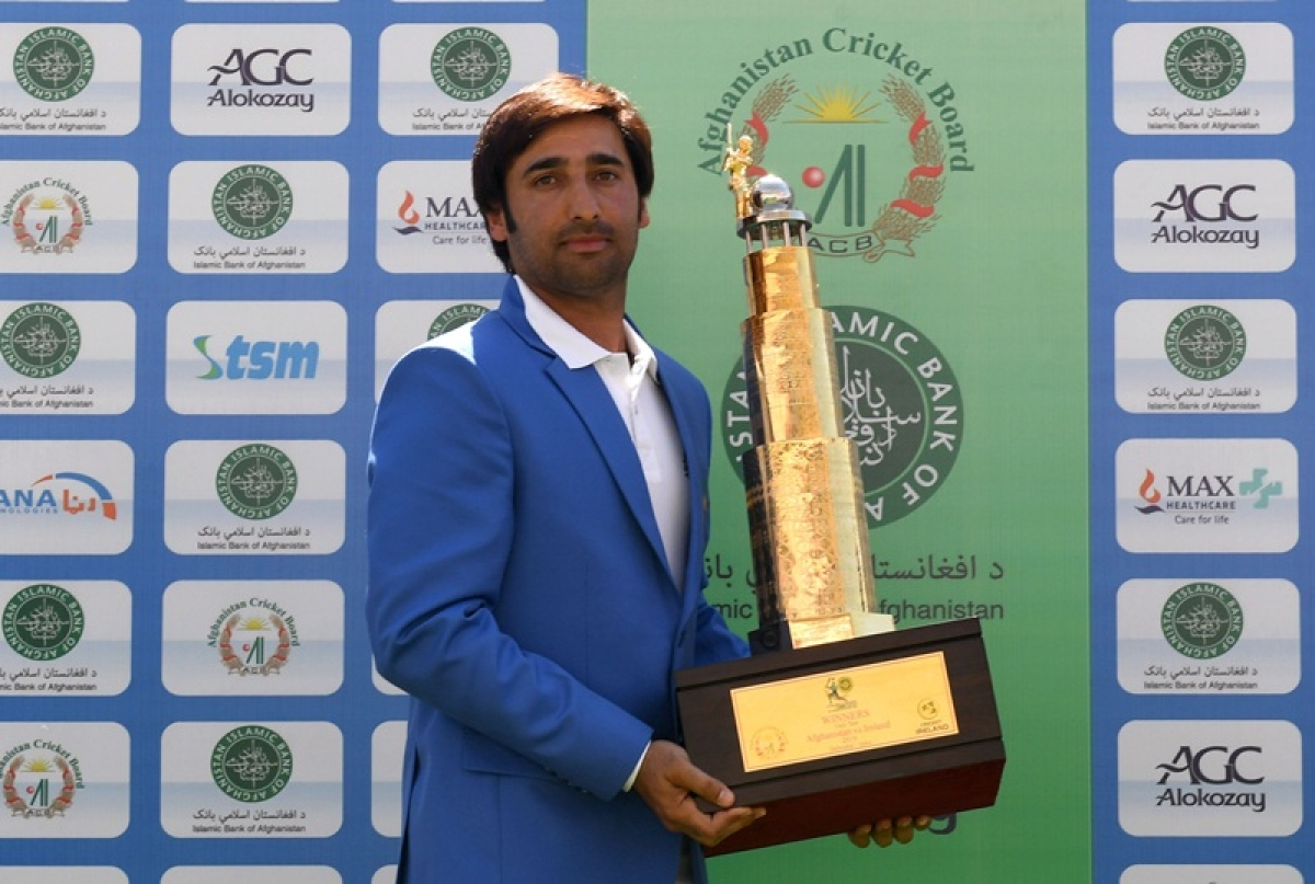 Afghanistan's captain Asghar Afghan poses with the trophy after winning the Test cricket match between Afghanistan and Ireland at the Rajiv Gandhi International Cricket Stadium in the northern Indian city of Dehradun on March 18, 2019. (Photo by Money SHARMA / AFP)