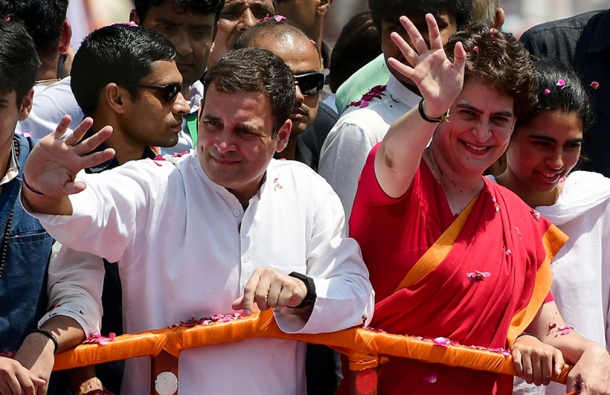 Indian National Congress party president Rahul Gandhi (L) and his sister Priyanka Gandhi (R) wave during a roadshow before filing his nomination for the upcoming general election at the district collector's office in Amethi on April 10, 2019. - India is holding a general election to be held over nearly six weeks starting on April 11, when hundreds of millions of voters will cast ballots in the world's biggest democracy. (Photo by SANJAY KANOJIA / AFP)