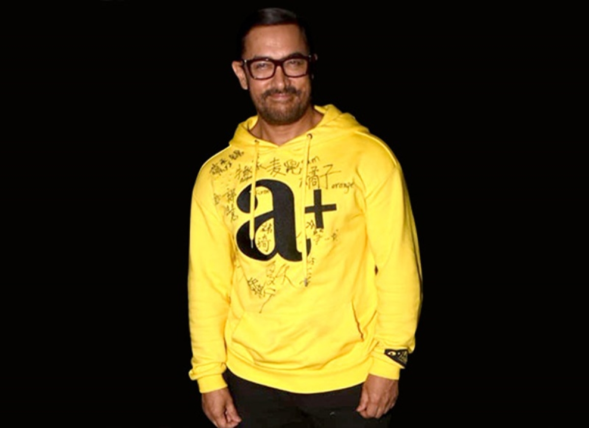 Aamir Khan sports a sweat-shirt signed by his fans from China