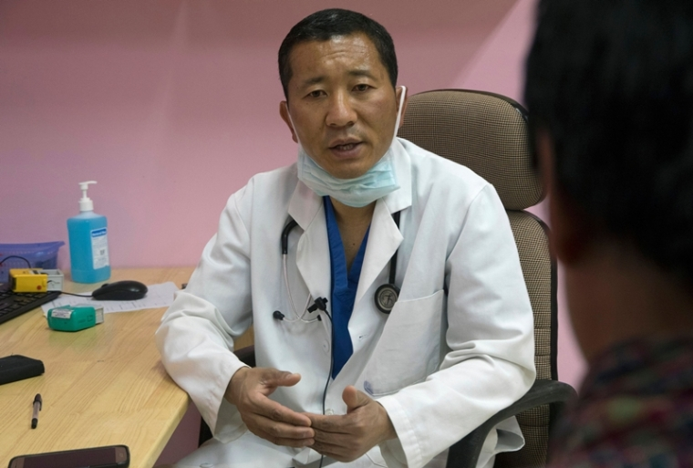 In this photo taken on March 30, 2019, Bhutan's Prime Minister Lotay Tshering is pictured at the National Referral Hospital in the Bhutanese capital Thimphu. - It's Saturday in Bhutan and in faded medical coat and crocs, Lotay Tshering has just completed urinary bladder repair surgery on a patient at the Jigme Dorji Wangchuck National Referral Hospital. But Tshering is no ordinary doctor. During the week, he also happens to be prime minister in the Himalayan kingdom famous for measuring citizens' Gross National Happiness. (Photo by Upasana DAHAL / AFP) / To go with: BHUTAN-POLITICS,FOCUS by Upasana DAHAL