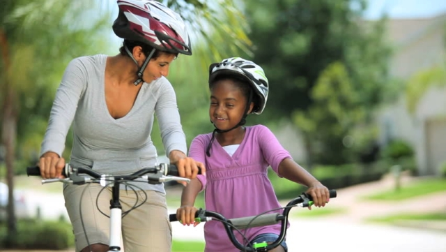 A mother bonding with her daughter by teaching her how to ride a bicycle