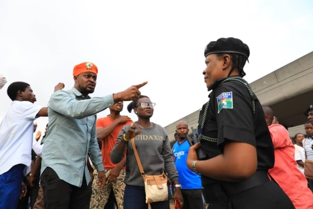 Angry protesters complaining to a female police officer