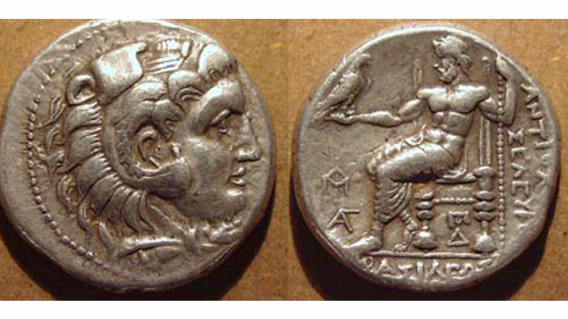 Coin issued by Selucus Nikator with Hercules wearing lion headdress on obverse and Zeus sitting on his throne holding an eagle on the reverse of the coin