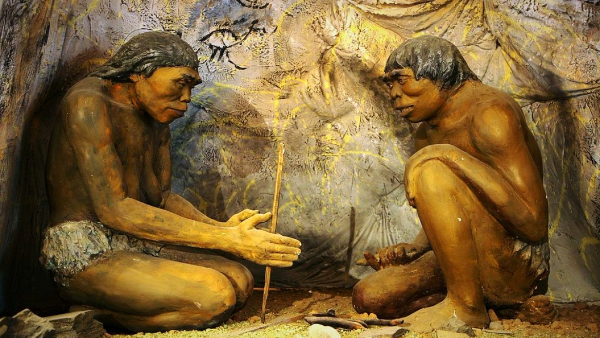 Diorama of earliest human species (Homo <i>erectus</i>) sheltered in a cave with rock art