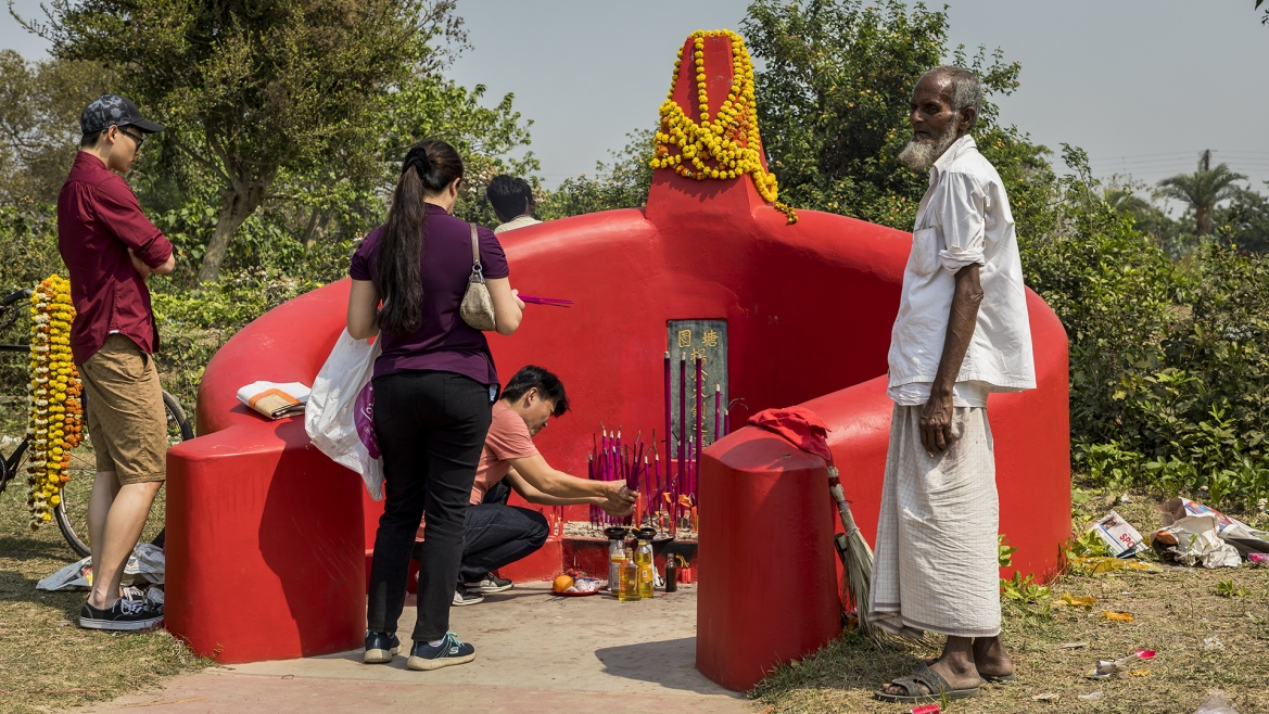 A Chinese family offers prayers at the tomb of Tong Atchew in Achipur