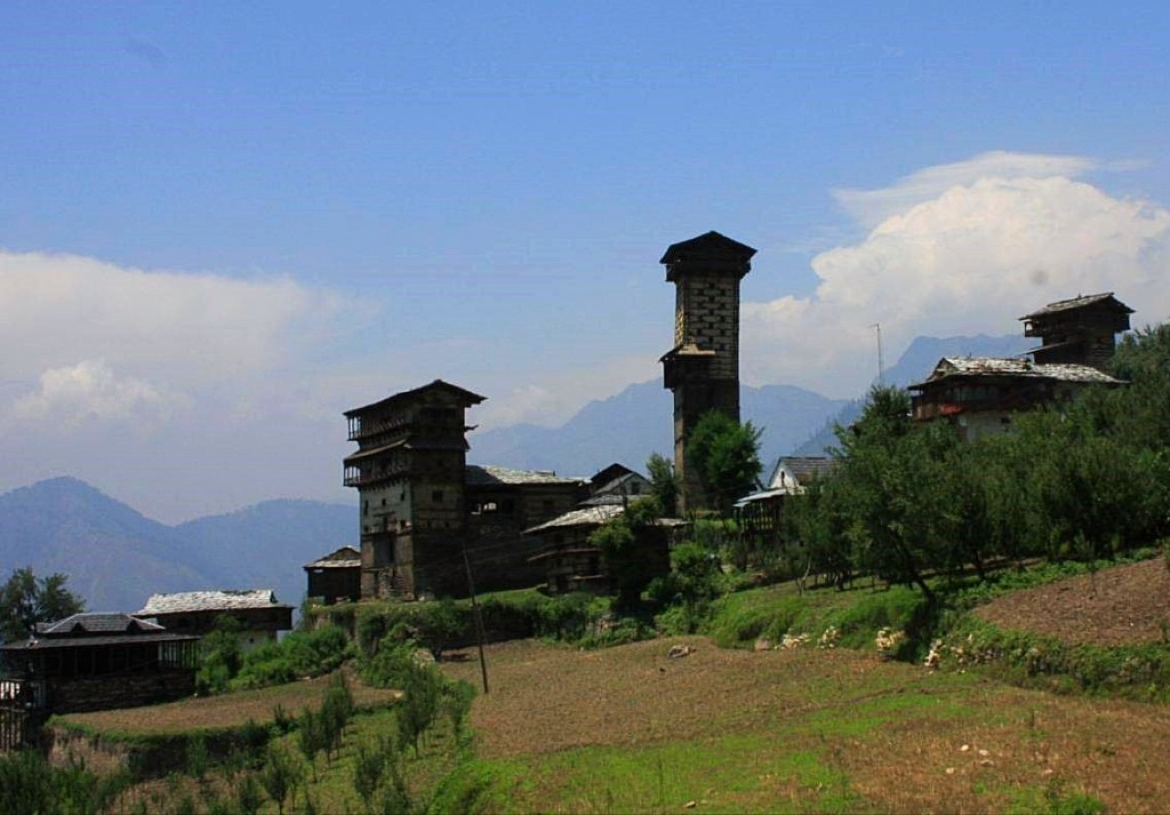 View of Chaini village, showing the soaring Chaini temple tower and the Thakurs' Kothi over the village