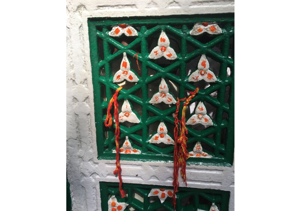 Painted medieval jaalis of tomb with knots of threads by visitors