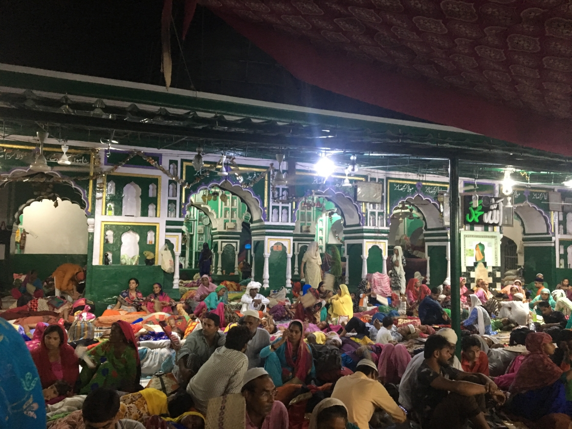 Pilgrims resting in courtyard close to medieval mosque at Dargah