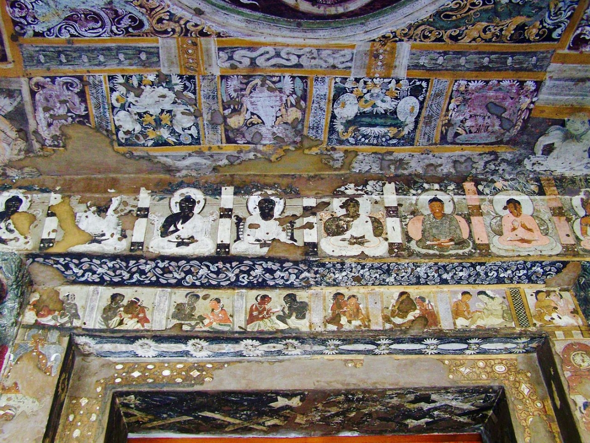 The ceiling is covered in decorative patterns, below is a row of Buddhas, and just above the doorway a couple of every day life scenes (cave 17)