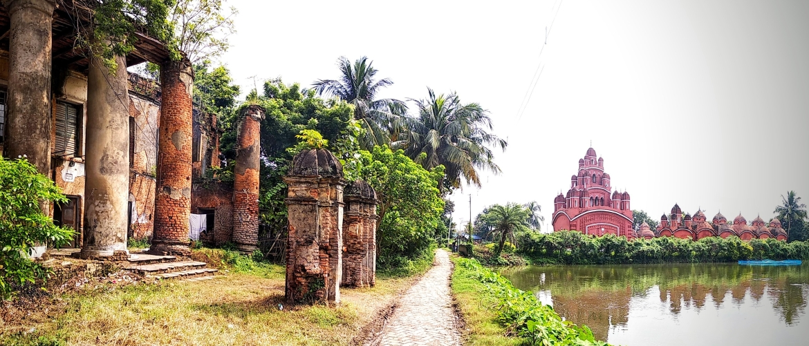 The huge columns of the Mustafi family mansion, Radha Kunja, and Ananda Bhairavi Temple complex on the banks of an adjacent water body in Sukharia-Somra