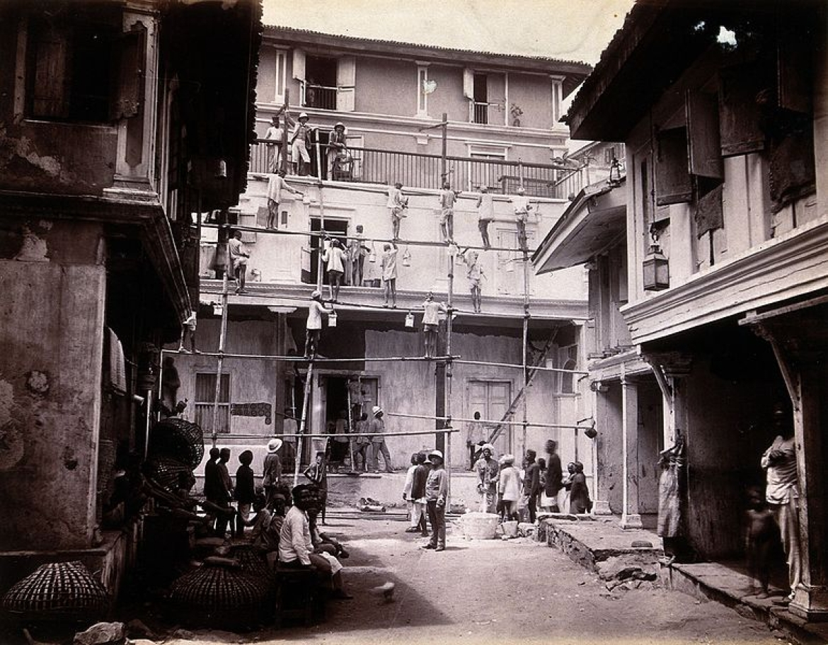 A plague house being whitewashed by men standing on scaffolding in Bombay